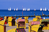 Beach chairs in the sunlight and sailing boats on the sea, Travemünde, Schleswig Holstein, Germany, Europe