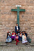 Indigenous believers sitting in front of a cross at the cathedral of Cusco, Peru, South America