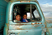 Indigenous children in a truck on the salt lake, Salar de Uyuni, Bolivia, South America