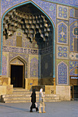 Women passing by Sheykh Lotfollah Mosque in Emam Khomeini Square. Esfahan, Iran