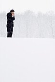 Businessman standing in snow flurry warming his hands, English Garden, München, Bavaria, Germany