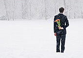 Businessman in a snowstorm hiding bouquet of tulips behind his back, English garden, Munich, Bavaria, Germany