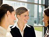 Three businesswomen talking and laughing, Munich, Bavaria, Germany