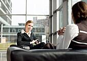 Businesswomen sitting in armchairs discussing, Munich, Bavaria, Germany