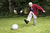 Senior man playing soccer, Bavaria, Germany