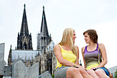 Two young german women sitting in front of the Cathedrale of Cologne, Cologne, North Rhine-Westphalia, Germany