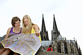 Two young women reading map, Cologne Cathedral in background, Cologne, North Rhine-Westphalia, Germany