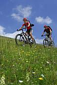 Couple mountain biking on alpine pasture, Bavarian foothills, Bavaria, Germany