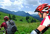 Junge Frau und Mann beim Mountainbiken über Almwiese, Wendelsteinregion, Bayerische Voralpen, Bayerische Alpen, Oberbayern, Bayern, Deutschland