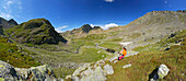 young woman resting on the way to notch Hörtlanger Scharte beneath Tagewaldhorn, panorama of cirque with Sulzspitze in background, Sarntal range, South Tyrol, Alta Badia, Italy