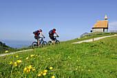 Zwei Mountainbiker bei einer Kapelle, Kampenwand, Chiemgau, Chiemgauer Alpen, Bayern, Deutschland