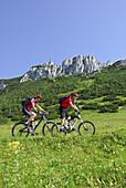 Paar beim Mountainbiken, Kampenwand, Chiemgau, Chiemgauer Alpen, Bayern, Deutschland