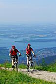 Paar beim Mountainbiken nahe der Steinlingalm mit Chiemseeblick, Kampenwand, Chiemgau, Chiemgauer Alpen, Oberbayern, Bayern, Deutschland