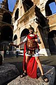 Man wearing uniform of Roman legionarie standing near Colosseum, Rome, Italy