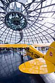 Yellow airplane under modern glass cupola in reflection in the museum hangar 7, Salzburg, Austria
