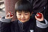 Kid with chinese balls. Beijing. China.