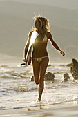 Adult, Adults, Beach, Beaches, Bikini, Bikinis, Blonde, Blondes, Board, Boards, Caucasian, Caucasians, Coast, Coastal, Color, Colour, Contemporary, Daytime, Exterior, Fair-haired, Female, Full-body, Full-length, Girl, Girls, Golden, Holiday, Holidays, Hum