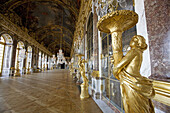 Golden statues holding lamps in the Hall of Mirrors, Palace of Versailles. France