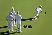Senior citizens playing lawn bowls