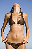 Adult, Adults, Bikini, Bikinis, Body, Brunette, Brunettes, Carnal, Carnality, Caucasian, Caucasians, Color, Colour, Contemporary, Dark-haired, Daytime, Exterior, Female, Figure, Hands on the waist, Holiday, Holidays, Human, Knees-up, One, One person, Outd