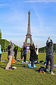 People doing Yoga, Eiffel Tower. Paris. France