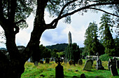 Round bastion and weathered graveyard under trees, Glendalough, County Wicklow, Ireland, Europe