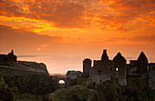 The ruins of Dunluce Castle on shore in the afterglow, County Antrim, Ireland, Europe