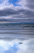 Message in a bottle on the beach under clouded sky, Portrush, County Antrim, Ireland, Europe