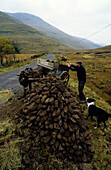 A farmer with a donkey cart peat cutting, Doo Lough Pass, County Mayo, Ireland, Europe