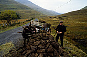 A farmer with donkey cart peat cutting, Doo Lough Pass, County Mayo, Ireland, Europe