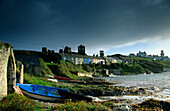 Houses and lighthouse on shore under thunder clouds, Roche's Point, County Cork, Ireland, Europe