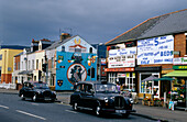 Vintage cars in front of facades of houses at Falls Road, Belfast, County Antrim, Ireland, Europe