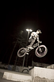A teenager jumping with his BMX bike at night, Wagram, Austria