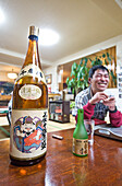 View at a bottle of sake and grinning man at a local, Hokkaido, Japan, Asia