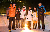 Two europeans and japanese women standing in the snow in the evening, Hokkaido, Japan, Asia