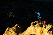 A couple on a mountain top, the man throwing a rope, Teide National Park, Tenerife, Canary Islands