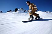 Boy snowboarding, See, Tyrol, Austria