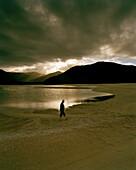 Ein Mann am Ufer des Awaroa Inlet bei Sonnenuntergang, Abel Tasman Nationalpark, Nordküste, Südinsel, Neuseeland