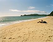 Menschen liegen am Waiharakeke Beach in der Sonne, Abel Tasman Nationalpark, Nordküste, Südinsel, Neuseeland
