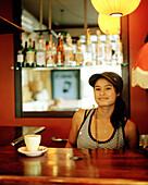 Young waitress at the counter at Fidels Café, Cuba Street 234, Wellington, North Island, New Zealand