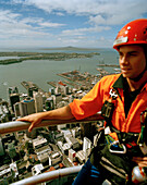 Young man with climbing equipment on top of Sky Tower, view at Central Business District and Waitemata Harbour, Auckland, North Island, New Zealand