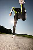 Man jogging along road, Strasslach-Dingharting, Bavaria, Germany