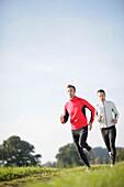 Two men running along dirt road, Munsing, Bavaria, Germany