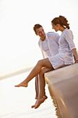 Couple sitting on a jetty, Ambach, Lake Starnberg, Bavaria, Germany