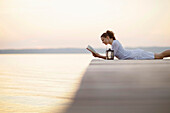 Woman lying on jetty at lake Starnberg while reading a book, Ambach, Bavaria, Germany