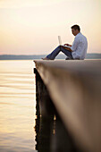 Man using a laptop while sitting on a jetty at lake Starnberg, Ambach, Bavaria, Germany
