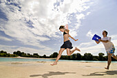 Teenage boy with bucket of water running after girlfriend, Freising, Bavaria, Germany