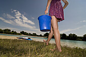 Young girl carrying a bucket of water, Freising, Bavaria, Germany