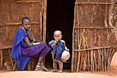 Massai woman with small child sitting in front of a mud hut, Tsavo, Kenya, Africa