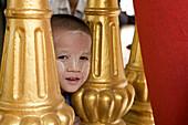 Face of a young burmese boy on the grounds of the Shwedagon Pagoda at Yangon, Rangoon, Myanmar, Burma